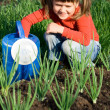 Stock Photo: Smiling girl with watering cis sitting near onion patch