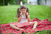 Little irritated girl preschooler sitting on plaid and grass — Stock Photo