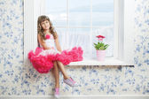 Romantic dreaming young girl sitting on windowsill near flower — Stock Photo