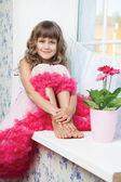 Primer plano de adolescente niña sentada en el alféizar de la ventana junto a la flor fresca — Foto de Stock