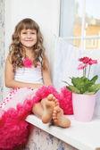 Girl teenager close-up sitting on windowsill near fresh flower — Stock Photo