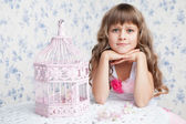 Tender dreamy romantic girl with wavy hair near open birdcage — Stock Photo