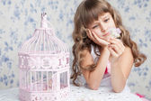 Tender dreamy romantic girl with wavy hair near open birdcage — Stock Photo