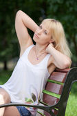Pretty blond woman sits with raised arms on park bench — Stock Photo