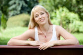 Young cheerful blond woman on the bench in summer park — Stock Photo