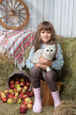 Portrait of girl villager with cat near pail, apples in hayloft — Stock Photo