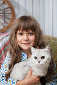 Portrait of sincere girl villager with cat on hands in barn — Stock Photo