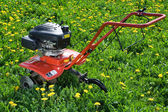 Tractor plough from back side on the flowering field — Stock Photo