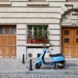 Blue retro moped parked near house on European cobblestone stree — Stock Photo