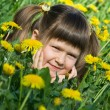Little cute girl is lying on the dandelion meadow — Stock Photo