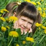 Little cute girl is lying on the dandelion meadow — Stock Photo