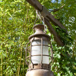 Royalty-Free Stock Photo: Kerosene oil lamp is hung up on green leaves background