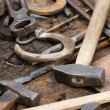 Stock Photo: Rusty blacksmith tools and horseshoes