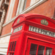 London symbol red telephone box on building facade background — Stock Photo #15340675