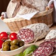 Slices salami on board, cherry tomatoes, olivas, bread in breadb — Lizenzfreies Foto