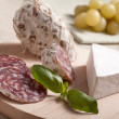 Traditional sliced salami on wooden board with brie, grapes, bas — Lizenzfreies Foto