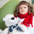 Stock Photo: Little sick girl with scarf embraces toy bear in bed close-up