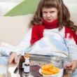 Stock Photo: Little sick girl with scarf in bed is taking medicine