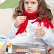 Little sick girl with scarf in bed is taking medicine — Stockfoto #15340891