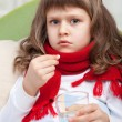 Little sick girl with scarf in bed is taking pill — Stock Photo #15340901