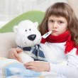 Stock Photo: Little sick girl with thermometer embraces toy bear in bed