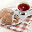 Cookies heart, brown sugar, spoon, black tea, saucer on tableclo — Стоковая фотография