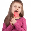 Little girl 7-8 years old licking red heart lollipop isolated — Stock Photo