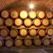 Wooden wine barrels are stored in winery cellar — Stock Photo #15340975