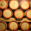 Wooden wine barrels are stored in winery cellar close-up - Stock Photo