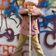 Cute little girl with scooter near graffiti painted wall — Stock Photo