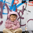Funny little girl with scooter near graffiti painted wall — Stock Photo