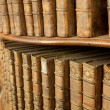 Covers of old medieval literary books on shelves in bookcase — Stock Photo
