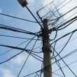 Stock Photo: Lamp pole and tangled electric wires