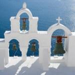 Calm sea, white church arch, cross, bells Island Santorini Greec — Stock Photo