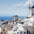 Traditional windmills in village Oia of Cyclades island Santorin - Stock Photo