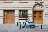 Blue retro moped parked near house on European cobblestone stree — Stock Photo