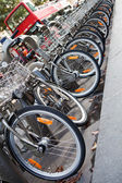 Double-decker tourist city bus and bicycle fleet on parking — Stock Photo