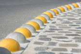 Curb separated asphalt road and cobblestone — Stock Photo