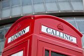 London symbol red public phone box on facade background — Stock Photo