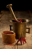 Cayenne pods in pounder and milled pepper on wooden table — Stock Photo