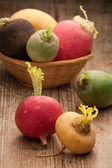 Group ripe variegated radishes in woven bowl on board — Stock Photo