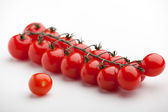 Bunch of ripe red cherry tomatoes close-up on white background — Stock Photo