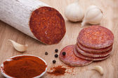 Traditional Hungarian paprika salami on board with garlic, black — Stock Photo