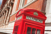 London symbol red telephone box on building facade background — Stock Photo