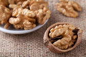 Kernels of nuts in plate and Circassian walnut on sackcloth — Stock Photo