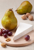 Green pears, cheese brie, walnuts and grapes on wooden board — Stock Photo