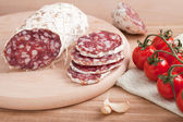 Traditional sliced salami on wooden board with garlic, cherry to — Stock fotografie