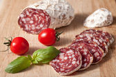 Traditional sliced salami on wooden board with basilic, cherry t — Stock Photo
