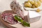 Traditional sliced salami on wooden board with brie, grapes, bas — Stock Photo