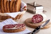 Serveras köksbord, sandwich på servett, salami, kornbod, s — Stockfoto